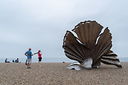 """Families admire 'Scallop', a 4 metre high steel sculpture of two interlocking scallop shells on Aldeburgh beach dedicated to Benjamin Britten. Hambling's Scallop (2003) stands on the north end of Aldeburgh beach. It is a tribute to Benjamin Britten and is pierced with the words """"I hear those voices that will not be drowned"""" from his opera, Peter Grimes, on 14th August 2020, in Aldeburgh, Norfolk, England."""