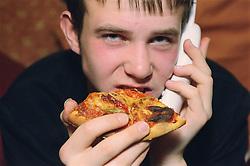 Teenage boy eating slice of pizza while holding telephone,