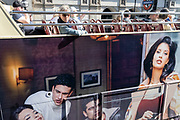 Unaware of the faces of models in a fashion ad, tourists sit on the open top deck of their tour bus during their journey across the capital, on 24th September 2021, in London, England.