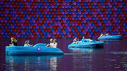 © Licensed to London News Pictures. 01/08/2018. LONDON, UK.  People in pedal boats pass by The London Mastaba on The Serpentine during the warm weather in Hyde Park.  Temperatures are forecast to increase back to the 30s in time for the weekend.  The sculpture by the artist Christo comprises 7,506 horizontally-stacked coloured barrels secured on a floating platform.  The geometric form takes inspiration from ancient mastabas from Mesopotamia and will be on display until 21 September 2018  Photo credit: Stephen Chung/LNP