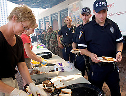 10 Sept 2005. New Orleans, Louisiana. Hurricane Katrina aftermath. <br /> The Turner foundation serves up hot food to anyone who cares to wait in line outside Harrah's casino on Canal Street. Kathy Mayhue serves up burgers to NYPD officers.<br /> Photo; ©Charlie Varley/varleypix.com