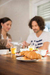 Croissants on dining table and mid adult couple having breakfast in the background, Munich, Bavaria, Germany
