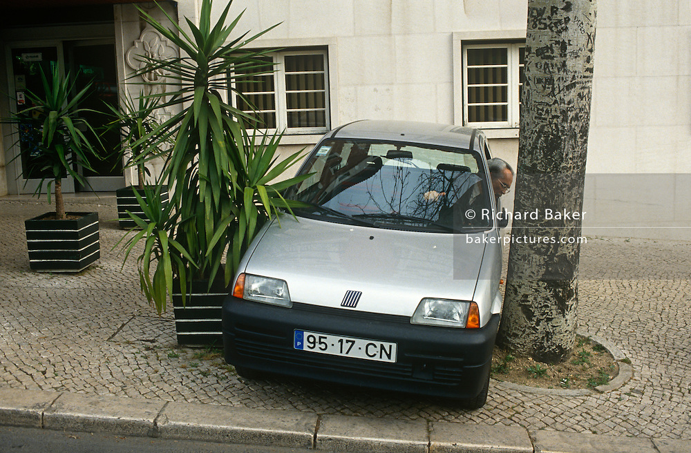 A local Portuguese man reverses his Fiat car into a narrow space between two trees on a Lisbon street pavement.
