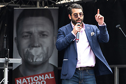 "© Licensed to London News Pictures. 14/07/2018. London, UK. RAHEEM KASSAM addresses the crowd . Supporters of EDL founder Tommy Robinson ( real name Stephen Yaxley-Lennon ) and US President Donald Trump hold a "" Welcome Trump "" rally on Whitehall . Trump is currently in Scotland and Robinson is in HMP Hull . Photo credit: Joel Goodman/LNP"