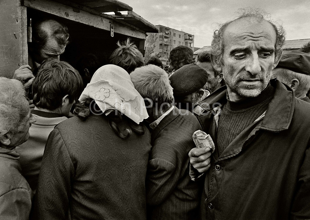 """Searching for food in """"free market"""" stall, Milot, Albania.<br /> Albania's communist economic system, with its strict central controls, egalitarian incentive system, and bias toward heavy industry, collapsed in the early 1990s, idling almost all of the country's production lines. Albania's government reported unemployment at about 30 percent, but unofficial 1991 estimates indicated that about 50 percent of the work force was jobless."""