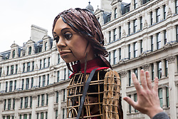 London, UK. 23rd October, 2021. Little Amal, a giant puppet of a Syrian refugee girl fleeing conflict, is welcomed at St Paul's Cathedral. The 3.5-metre puppet, which is nearing the end of an 8,000km journey from the Turkish-Syrian border to Manchester in support of refugees, climbed the steps of St Paul's Cathedral to present a wood carving of a ship at sea from St Paul's birthplace at Tarsus in Turkey to the dean.