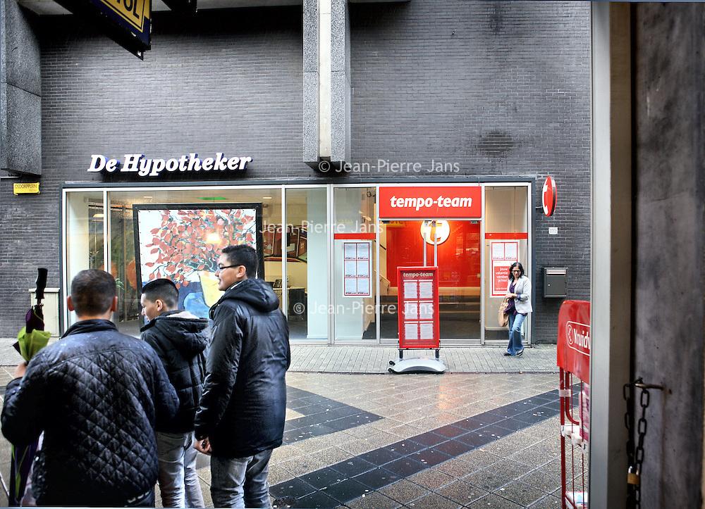 Nederland, Amsterdam , 16 juli 2012..De werkeloosheid onder jonge allochtonen schijnt erg hoog te zijn. In ieder geval een stuk hoger dan onder autochtonen jongeren..Op de foto enkele allochtone jongeren passeren een tempo-team uitzendbureau op het Osdorpplein..Foto:Jean-Pierre Jans