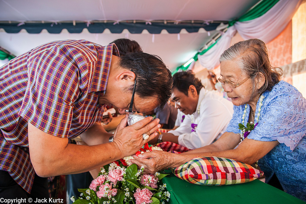 13 APRIL 2013 - BANGKOK, THAILAND: A man makes merit by washing the hands of an elderly woman in scented water during a Songkran observance at Bangkok City Hall. The Songkran tradition of throwing water on people started with the traditional hand washing. Songkran is the traditional Thai New Year's Festival. It is held April 13-16. Many Thais mark the holiday by going to temples and making merit by giving extra alms to monks or offering extra prayers. They also mark Songkran with joyous water fights. Songkran has been a national holiday since 1940, when Thailand moved the first day of the year to January 1.    PHOTO BY JACK KURTZ