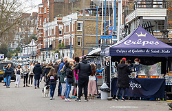 """© Licensed to London News Pictures. 28/03/2021. London, UK. Members of the public queue up at a food stall along the River Thames in Putney, South West London ahead of the end of the """"Stay at Home"""" advice from tomorrow with temperatures expecting to reach up to 23c next week. On Monday 29 March, the """"Stay at Home"""" advice will end with people being allowed to meet up within the """"rule of six"""". Playing golf, tennis and organised outdoor sports will also be allowed as England starts to unlock after a year of Covid-19 restrictions. Photo credit: Alex Lentati/LNP"""