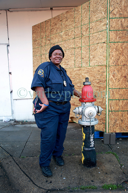 23 February 2014. New Orleans, Louisiana.<br /> Claudia Woods, a guard with District Security guards a boarded up Banksy original painting after audacious thieves attempted to chop the artwork from the wall of an old abandoned store in New Orleans on the corner of North Rampart and Kerlerec street. The building will be guarded 24 hours a day for the time being.<br /> Photo; Charlie Varley/varleypix.com