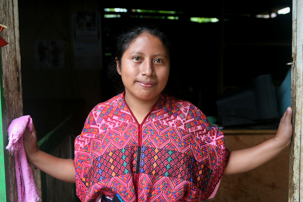 Indigenous woman Alberta Guarchaj, Vice-President of the Nahuala coffee coop, stands in the doorway of her home.