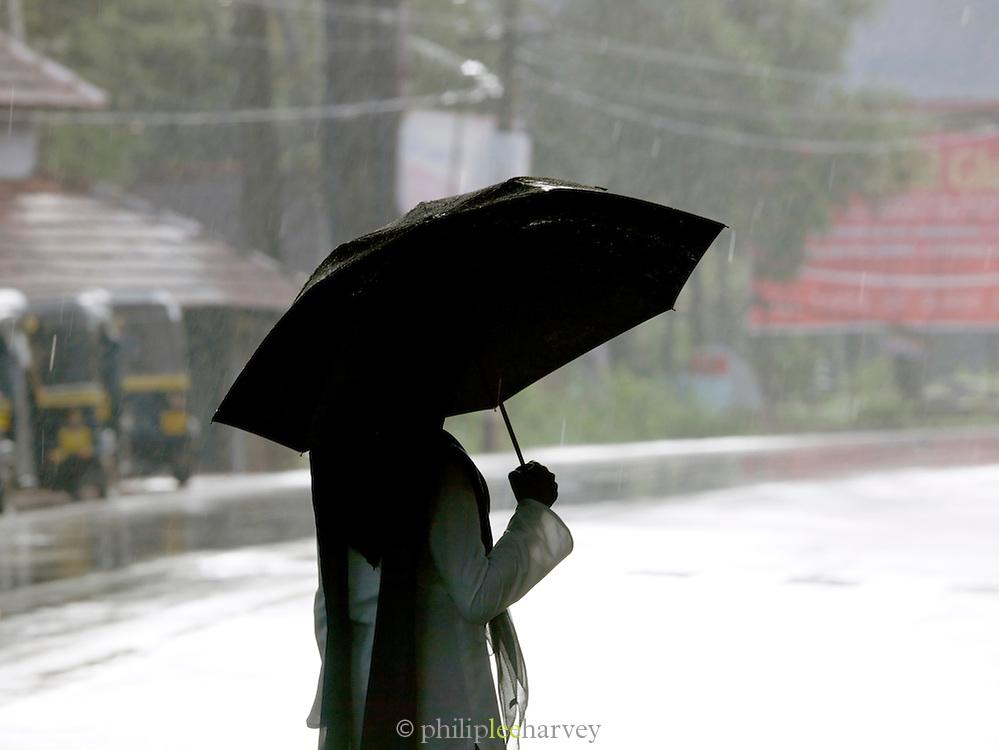 Woman shelters under an umbrella during the monsoon rain, Cochin, Kerala, India