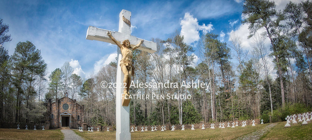 Panorama of crucifix and Chapel with graveyard at Ave Maria Grotto, Cullman, AL.