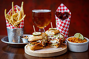 Fried chicken sandwich along side fries, brown sugar bacon, and house corn nuts at The Eagle on Bardstown Rd.