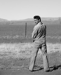 Black and white picture of man in jeans looking back over his shoulder while peeing