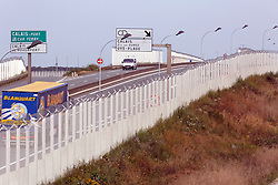 Lorries drive along a protection fence, preventing access to a circular road leading to the port of Calais, next to the Jungle migrant camp, in Calais, northern France, on September 22, 2016. Up to 10,000 migrants are now living at the camp and are using desperate and violent measures to try and board trucks heading for the UK. Photo by Sylvain Lefevre/ABACAPRESS.COM