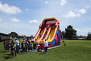 Children slide down an inflatable slide during the Pomeroy Multicultural Festival at Pomeroy Elementary School in Milpitas, California, on April 25, 2015. (Stan Olszewski/SOSKIphoto)