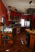 Red kitchen is part of a home, decorated by feng shui rules. The home is a beach front home in Los Barriles, Baja California Sur. <br /> Photo is part of set of photographs of a beach front home in Los Barriles, Baja California Sur, Mexico.