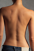 Side lit close up of a bare woman's back with the woman wearing jeans