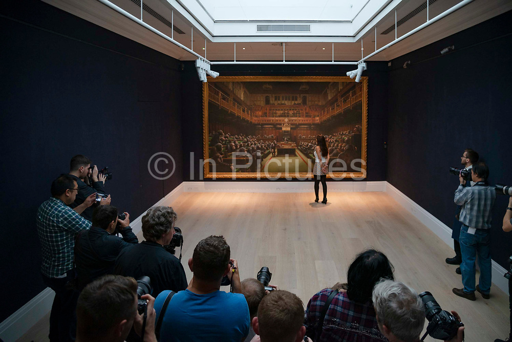 Press photographers takes photos as a gallery assistant views  Banksy's Desolved Parliament at a press preview at  Sothebys auction house in London, United Kingdom on 27th September 2019. The work is estimated to reach GBP 1.5 - 2 million when it goes under the hammer.