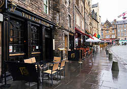 Scotland, Scotland, UK. 24 May 2021. Unseasonable cool and damp weather in Edinburgh meant that there were few customers in the many outdoor bars , cafes and restaurants in the city centre, With few tourists in the capital the streets remain much quieter than normal. Pic; Outdoor seating for bars and restaurants lie empty at lunchtime in the popular Grassmarket. Iain Masterton/Alamy Live News