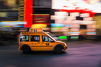 A New York City taxi cab rushes through Times Square at night.