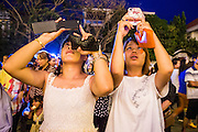 """30 JANUARY 2013 - PHNOM PENH, CAMBODIA:    Women use their smart phones to photograph the crematorium for late Cambodian King Norodom Sihanouk in Phnom Penh. Sihanouk (31 October 1922- 15 October 2012) was the King of Cambodia from 1941 to 1955 and again from 1993 to 2004. He was the effective ruler of Cambodia from 1953 to 1970. After his second abdication in 2004, he was given the honorific of """"The King-Father of Cambodia."""" Sihanouk held so many positions since 1941 that the Guinness Book of World Records identifies him as the politician who has served the world's greatest variety of political offices. These included two terms as king, two as sovereign prince, one as president, two as prime minister, as well as numerous positions as leader of various governments-in-exile. He served as puppet head of state for the Khmer Rouge government in 1975-1976. Most of these positions were only honorific, including the last position as constitutional king of Cambodia. Sihanouk's actual period of effective rule over Cambodia was from 9 November 1953, when Cambodia gained its independence from France, until 18 March 1970, when General Lon Nol and the National Assembly deposed him. Upon his final abdication, the Cambodian throne council appointed Norodom Sihamoni, one of Sihanouk's sons, as the new king. Sihanouk died in Beijing, China, where he was receiving medical care, on Oct. 15, 2012. His cremation is scheduled to take place on Feb. 4, 2013. Over a million people are expected to attend the service.        PHOTO BY JACK KURTZ"""
