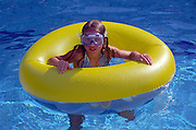 Model released picture of girl playing in swimming pool with inflated plastic buoyancy ring