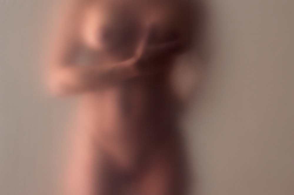 Side lit nude woman behind diffusion screen conducting breast examination