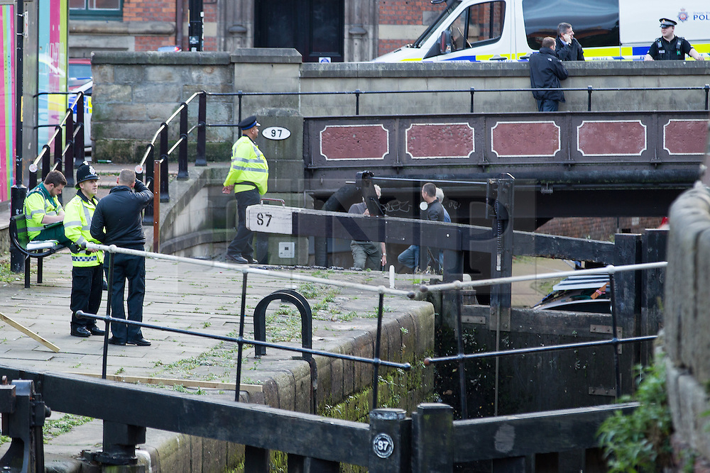 """© Licensed to London News Pictures . Manchester , UK . FILE PICTURE DATED  06/10/2013 of police waiting as the lock is drained , to recover a body . Police pulled a body from The Bridgewater Canal in Manchester , adjacent to the City's """" Gay Village """" on Canal Street . Greater Manchester Police have issued a statement after suggestions that a number of deaths in and around Manchester's canals may be linked to a serial killer , named in local folklore as """" The Pusher """" . The statement said """" Absolutely no evidence whatsoever of foul play has been established """" . Photo credit : Joel Goodman/LNP"""