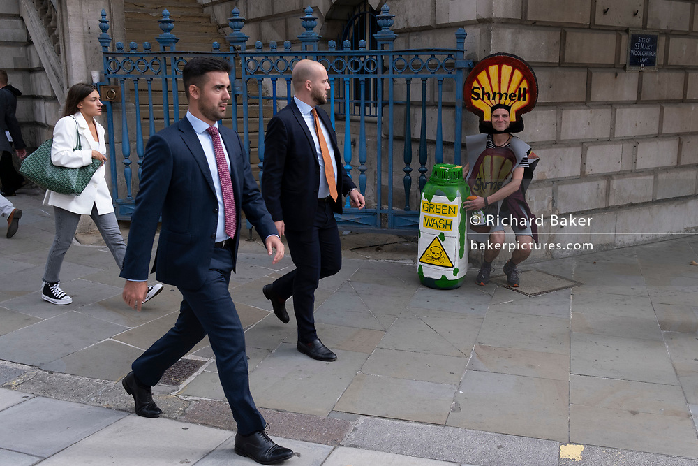 Businessmen walk past a climate Change Extinction Rebellion protester concerened about the fossil fuel economy during the occupation of Bank in the City of London, the capital's financial district, on 2nd September 2021, in London, England.