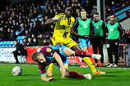Scunthorpe United forward George Thomas is tackled by Burton Albion forward Lucas Akins during the The FA Cup 1st round match between Scunthorpe United and Burton Albion at Glanford Park, Scunthorpe, England on 10 November 2018.