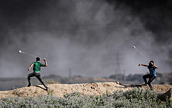 June 9, 2017 - Gaza, Jabalia, Gaza Strip - Palestinian protesters take cover during clashes with Israeli security forces following a demonstration against the blockade protest near the border fence east of Jabalia refugee camp. (Credit Image: © Nidal Alwaheidi/Pacific Press via ZUMA Wire)