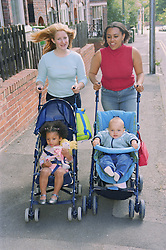 Young mothers pushing children in pushchairs along pavement; talking and smiling,