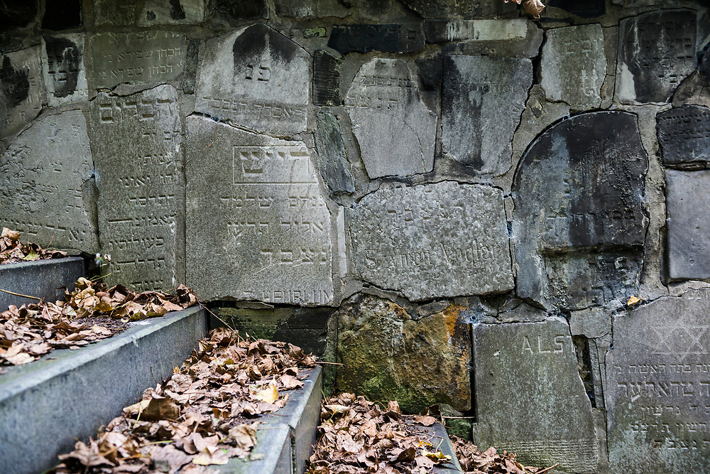 Old grave tombstones line a wall in the New Jewish Cemetery in Kraków, Poland. The cemetery was founded in 1800 and is located in the historic Jewish neighborhood of Kazimierz. During World War II the Nazis sold or otherwise used the Jewish tombstones for other purposes. Following the war many tombstones were recovered and the cemetery renovated.