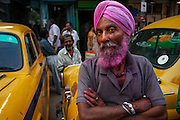 A yellow taxi cab driver during Holi.
