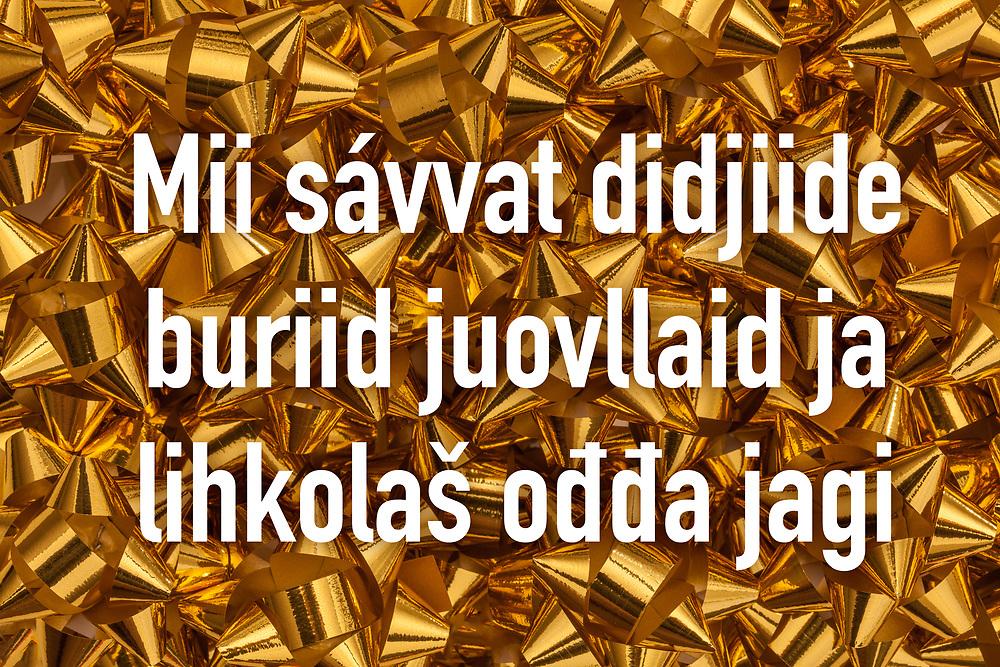 Jul- og nyttårshilsen-design med nord-samisk tekst «Mii sávvat didjiide buriid juovllaid ja lihkolaš ođđa jagi». Hvit tekst på bakgrunn av gull gaverosetter.