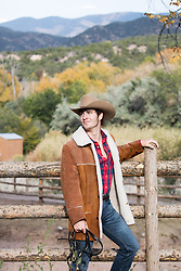 rugged cowboy in a sheepskin coat on a ranch