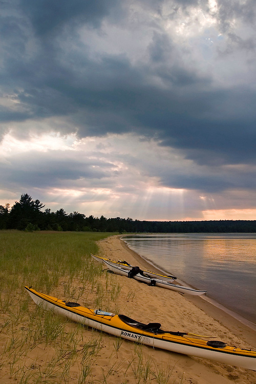 A group of sea kayaks on Trout Bay beach on Grand Island National Recreation Area in Munising Michigan with dramatic skies sky.