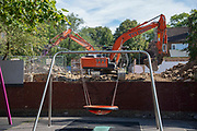 Graffiti on a wall seems to make a face with a childs swing in the foreground as men use a digging machine on a demolition site in close proximity to a childrens playground in London, United Kingdom on 13th September 2019.