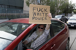 November 12, 2016 - Los Angeles, California, United States - A motorist holds a sign while waiting for crowd of anti-Trump protesters to pass by in Los Angeles, California on November 12, 2016. According to the LAPD an estimated crowd of nine thousand people participated, making this the largest anti-Trump protest to date in the city. (Credit Image: © Ronen Tivony/NurPhoto via ZUMA Press)