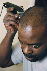Man using electric razor to shave his head,