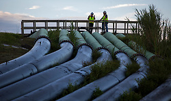 September 13, 2017 - Belle Glade, Florida, U.S. - Workers checks bypass pipes at the Herbert Hoover Dike culvert 12A replacement project. Debris from Hurricane Irma was cleaned out of the bypass pipes so that canal water can be  pumped into Lake Okeechobee near Belle Glade, Florida on September 13, 2017. (Credit Image: © Allen Eyestone/The Palm Beach Post via ZUMA Wire)