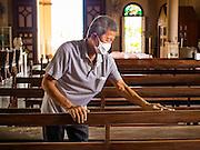 14 SEPTEMBER 2016 - BANGKOK, THAILAND: A volunteer cleans the interior of Santa Cruz church in Bangkok. Santa Cruz is one of the first Catholic churches in Bangkok. It was established by Portuguese mercenaries serving King Taksin the Great in 1770.         PHOTO BY JACK KURTZ