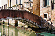 """Water reflects morning sun which shimmers underneath a pedestrian bridge in the Ghetto, in Cannaregio sestiere, Venice (Venezia), Italy, Europe. The Venetian Ghetto was where Jews were compelled to live under the Venetian Republic starting in 1516, and from this the word """"ghetto"""" originates. Venezia, founded in the 400s AD, is capital of Italy's Veneto region, named for the ancient Veneti people from the 900s BC. The romantic City of Canals stretches across 100+ small islands in the marshy Venetian Lagoon along the Adriatic Sea, between the mouths of the Po and Piave Rivers. The Republic of Venice was a major maritime power during the Middle Ages and Renaissance, a staging area for the Crusades, and a major center of art and commerce (silk, grain and spice trade) from the 1200s to 1600s. The wealthy legacy of Venice stands today in a rich architecture combining Gothic, Byzantine, and Arab styles. Venice and the Venetian Lagoon are honored on UNESCO's World Heritage List."""