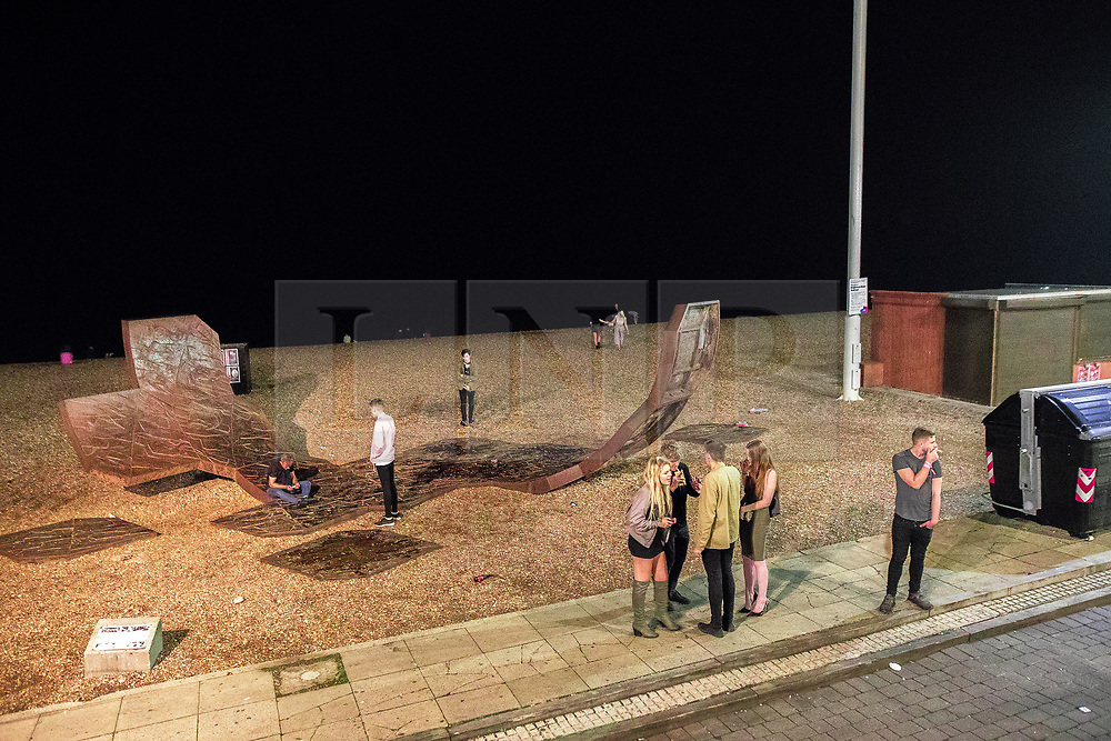 © Licensed to London News Pictures . 26/09/2017. Brighton, UK. People stand around monuments amongst the shingles of Brighton beach . Revellers at the end of a night out in Brighton during Freshers week , when university students traditionally enjoy the bars and clubs during their first nights out in a new city . Photo credit: Joel Goodman/LNP
