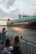 Savannah, Georgia - July 30, 2021: visitors to Savannah take pictures as a departing vehicle carrier named Tamesis sails past on the Savannah River on its way to the ocean.