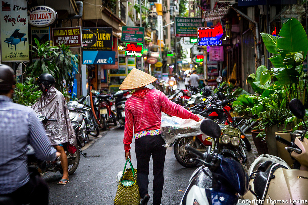 Fine Art:<br /> July, 2017, Old Quarter, Hanoi: Crowded alley with Asian lady wearing conical hat and a red top.  Contrasty and colorful. RAW to Jpg