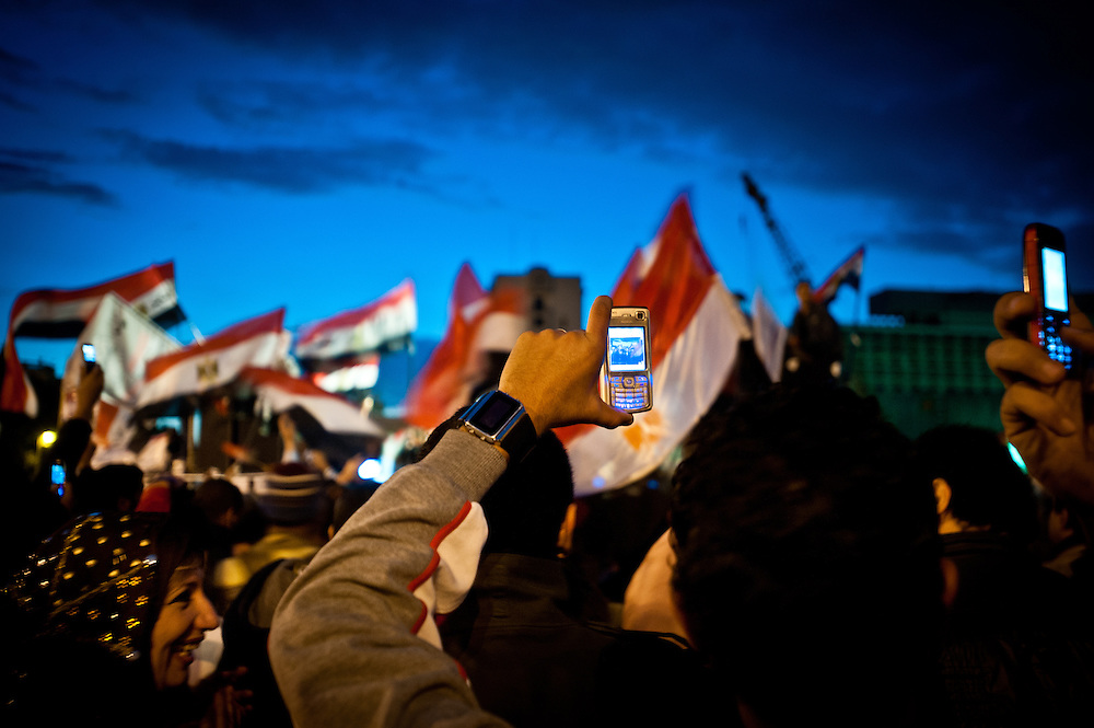 On the eighteenth day of protests in Tahrir Square, Cairo, Egyptian protesters take videos with their cellphones while others wave flags and chant slogans calling for the ouster of President Hosni Mubarak, who has ruled the country for thirty years. Technology played a major part in the spread of the Egyptian revolution, with thousands of protesters posting photos and videos on social media services like Facebook and Twitter.