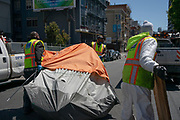 Department of Public Works employees remove tents from the street in the Tenderloin neighborhood of San Francisco, CA on June 16, 2020. Some unhoused residents who were moved into hotels or Safe Sleeping Sites after agreeing to having their tents destroyed.